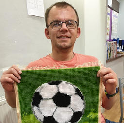Carl has finished his needlepoint.