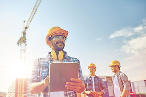 business, building, industry, technology and people concept - smiling builder in hardhat with tablet