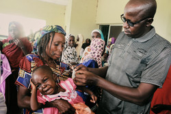 A physician conducting  a Mid-Upper Arm Circumference to evaluate the nutrition status of a child, K