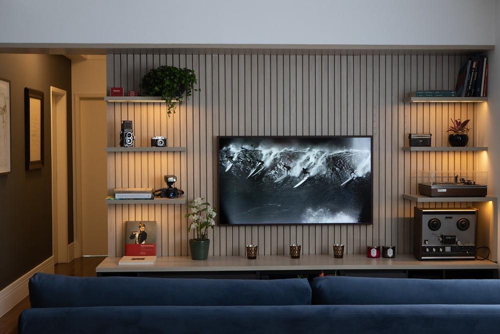 Estante multimídia para coleções de equipamentos de som e imagem. Painel de marcenaria para TV. TV que exibe quadros e fotografias.