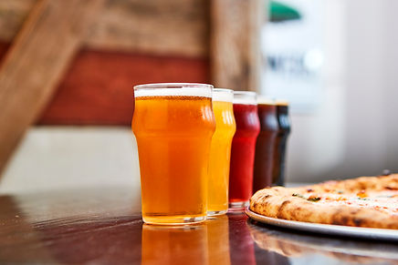 draft beers next to a pizza