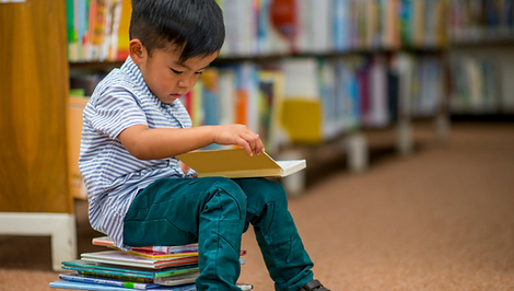 preschooler sitting on a pile of books and reading a book in a library