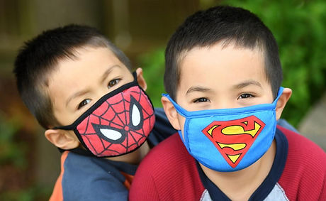 Two preschool boys wearing cloth masks with superhero decoration