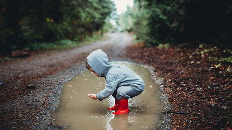 preschool child wearing boots standing in rain puddle
