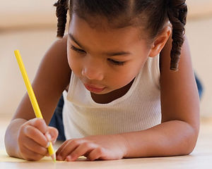 Preschool girl writing on paper with pencil