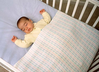 Baby with blanket in cot2.jpg
