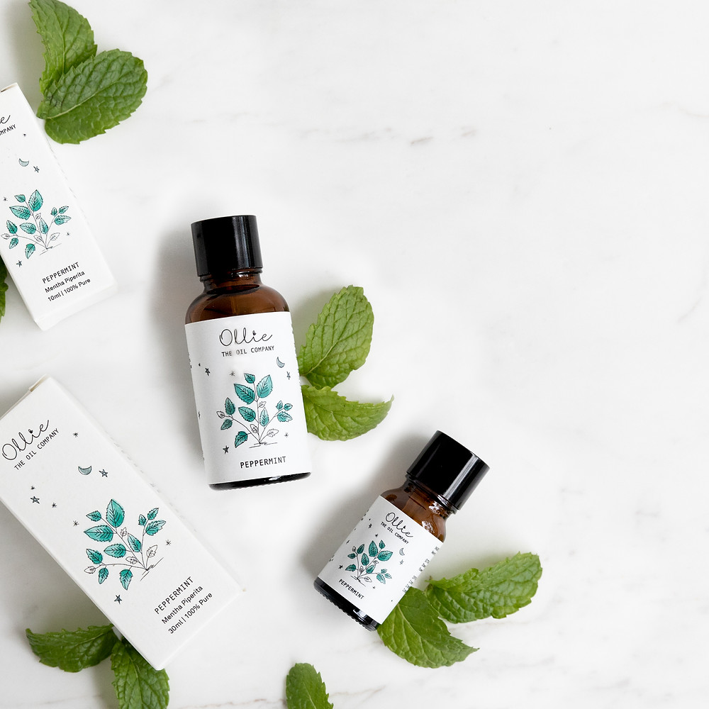 Peppermint oil with packaging on a background of mint leaves