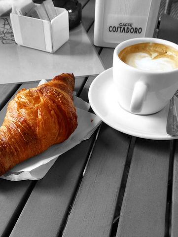 Foto av cappuccino och croissant, som är en typisk italiensk frukost.