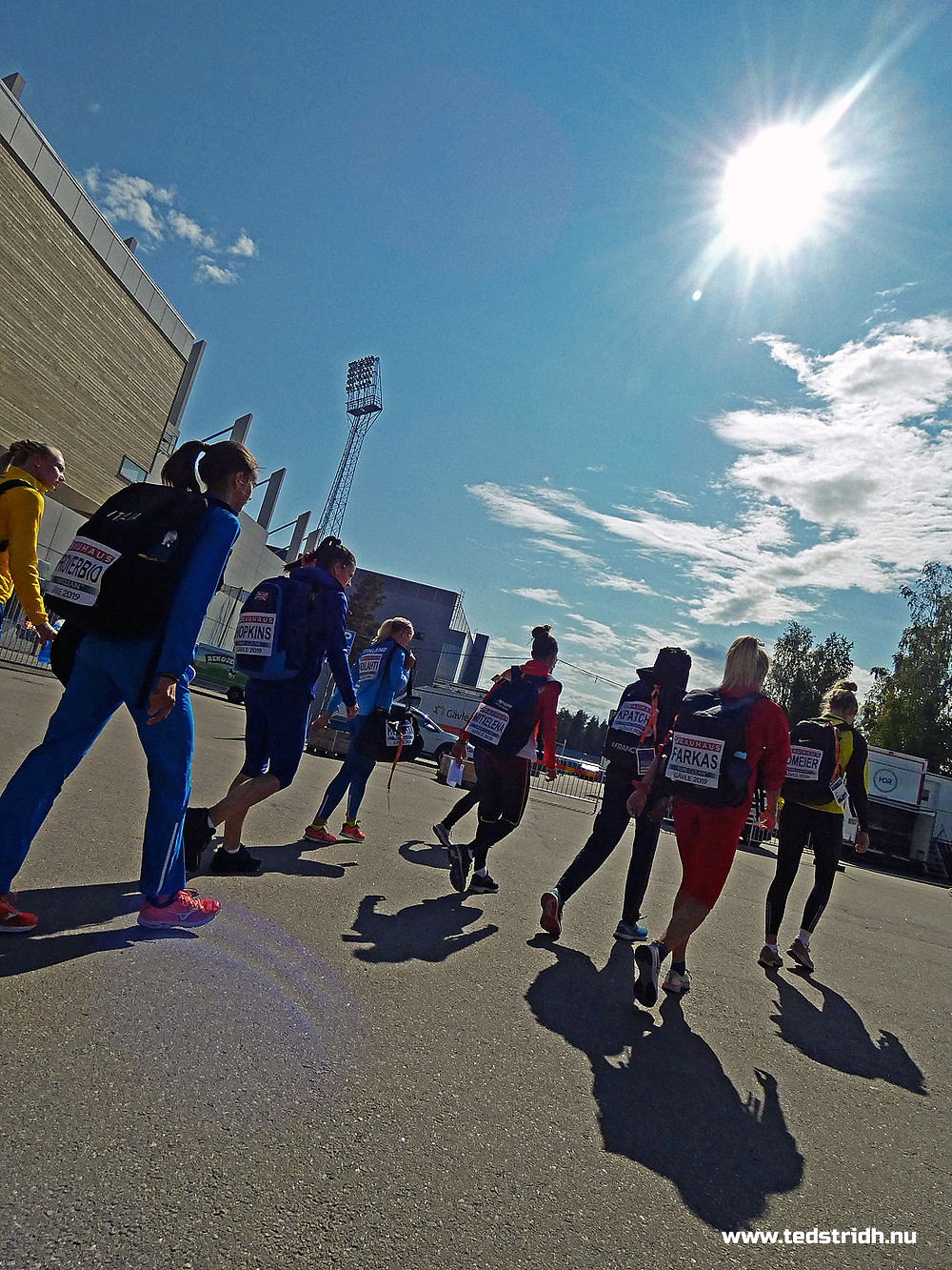 Women athletes are walking in the sunshine on their way to their competition. The athletes comes from Finland, Germany, Italy and Sweden.