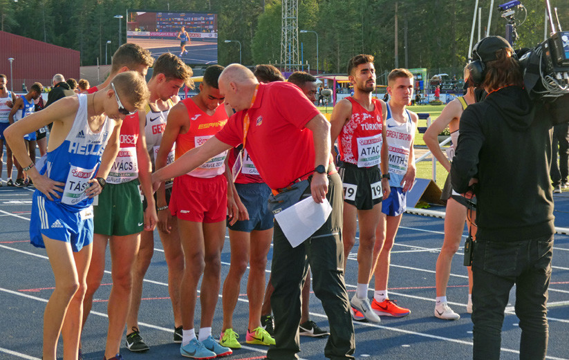 A steward is talking to the athletes who are standing at the starting line before the start of the competition. In the background a cameraman is filming the event.