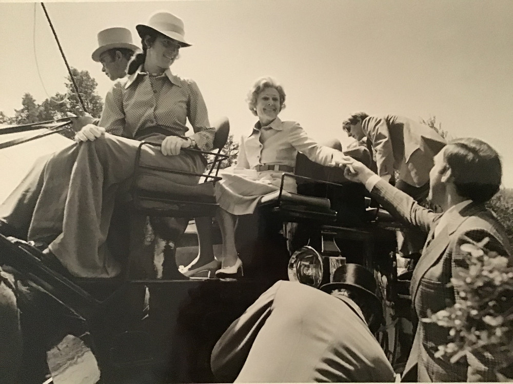 Keister Evans reaches to assist Former First Lady Pat Nixon from her four-in-hand horse drawn carriage.