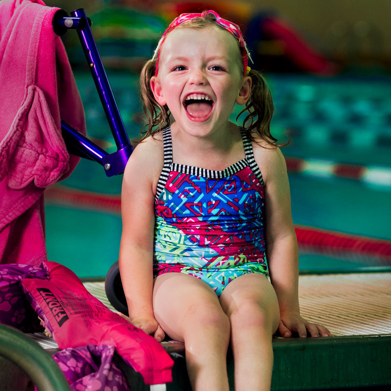 little girl sits by the pool in front of her walker, laughing
