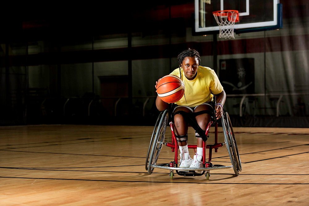 girl sitting in wheelchair dribbles basketball in front of a basketball net