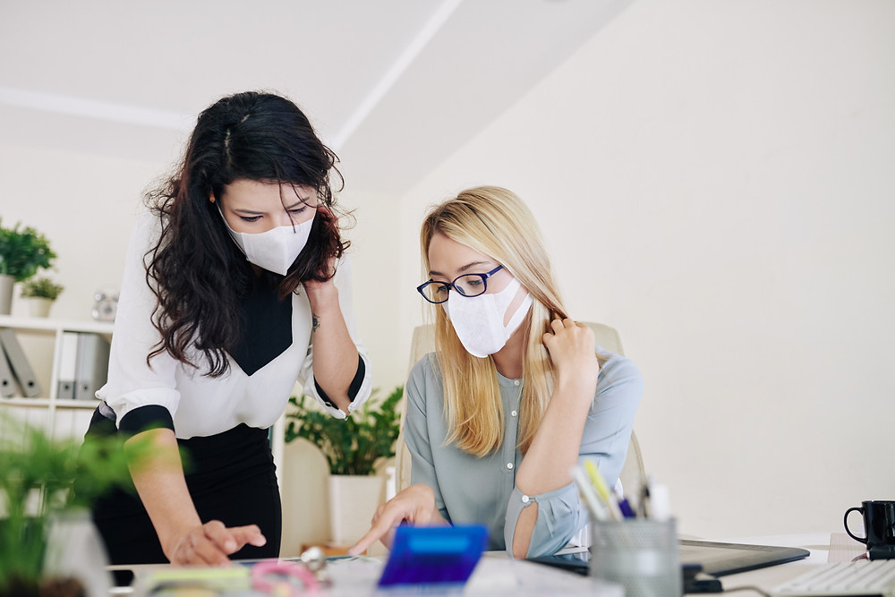 Two women wearing masks collaborate in the office in a post COVID-19 world