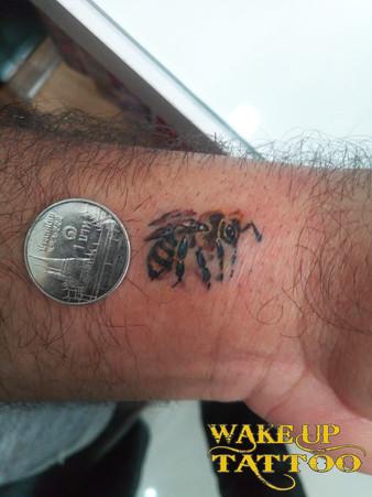 Small bee tattoo by Wake up Tattoo Phuket