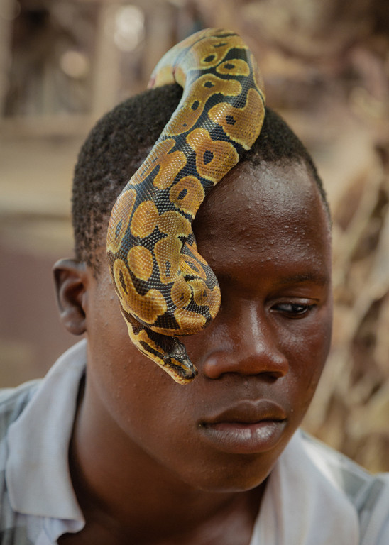 Bertin plays with a python. Snakes are used generally to protect newborns. Teeth of vipers, once pulverized, are injected in the body in order to get protection from snake bites.