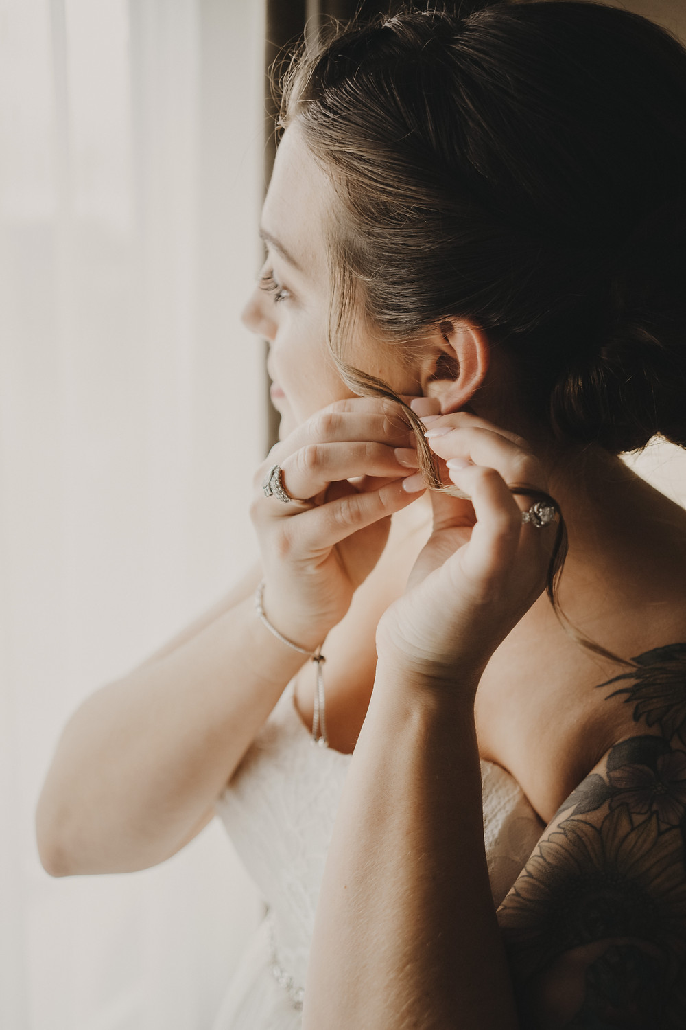 Bride adds the finishing touches with earrings