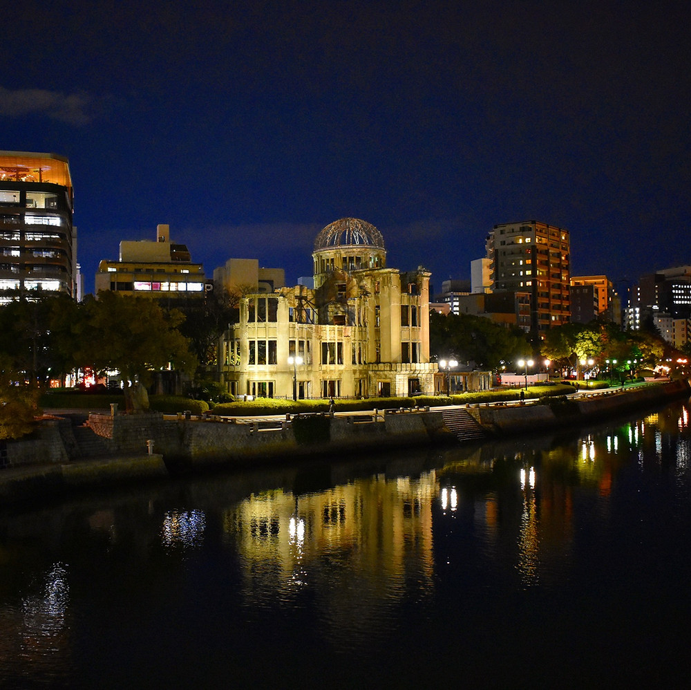Hiroshima's famous Atomic Bomb Dome lit up at night along the Motoyasu River.