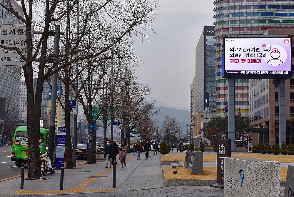 Just past City Hall in Seoul a billboard displays a PSA about what to do to seek treatment for COVID-19