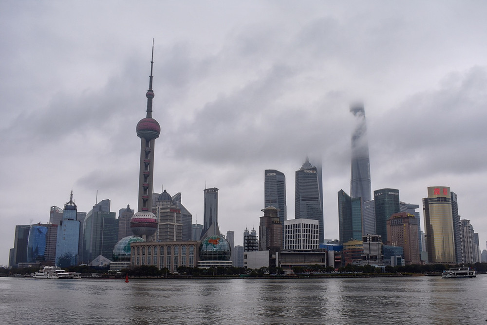 Shanghai's skyline from across the Huangpu River. The Oriental Pearl Tower can be seen through the low lying clouds. The world's second tallest tower, the Shanghai Tower, is hidden behind  the cloud cover.