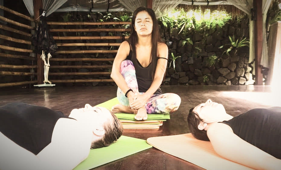 Patricia is sitting and the other participants are laying down in meditation.