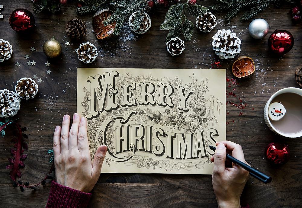 Person schreibt Merry Christmas auf Tafel