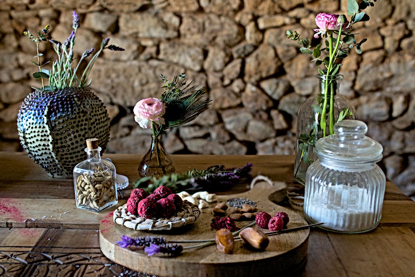 Table with raspberry & chia bliss balls with some raw ingredients around. Some lavender and rose flowers decorate the image.