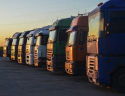 Multiple trucks park in a large parking
