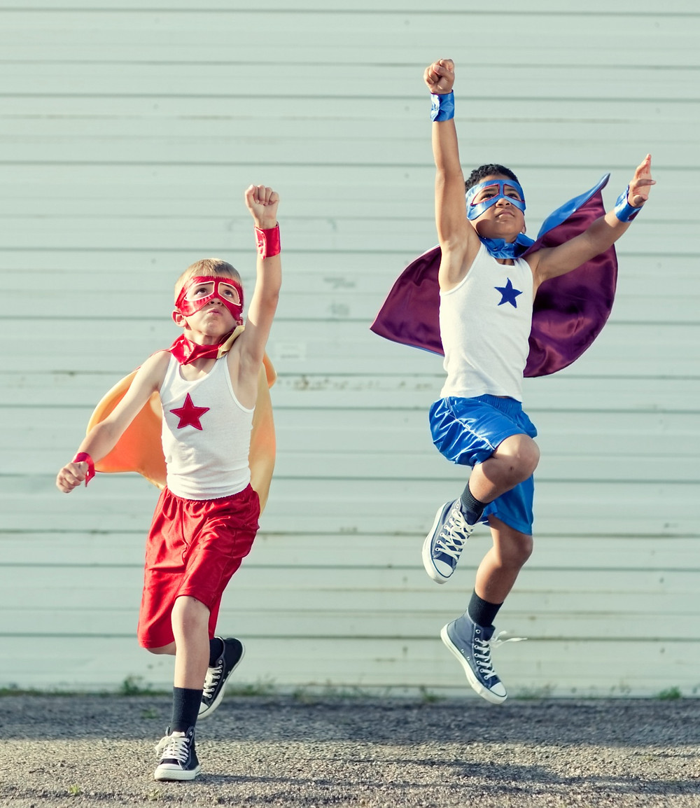 Two kids in superhero costumes jumping