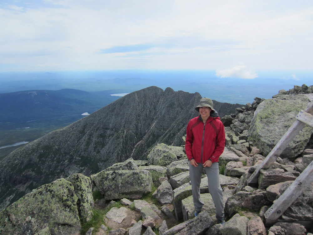 Katie standing at the stop of Mt. Katahdin in Maine with the Knife's Edge trail in the background.