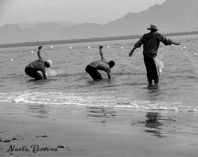A imagem mostra três pescadores manuseando uma rede de pesca no mar.