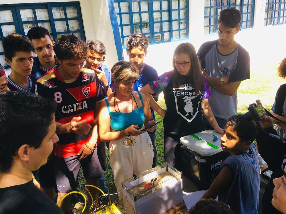A imagem mostra uma professora realizando um experimento com correntes elétricas. Ao redor da professora aparecem alunos observando o experimento.