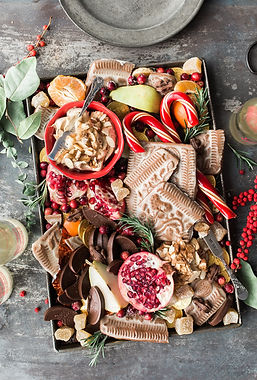 A plate filled with traditional Christmas treats. Gingerbread, candy canes and merry wishes galore._