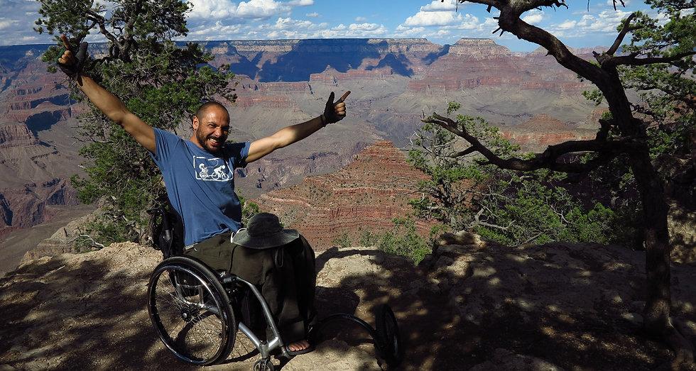 Reinfried Blaha beim Reisen im Rollstuhl in Freudenpose vor dem Grand Canyon, USA