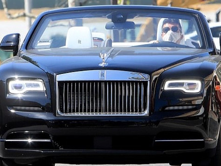 Simon Cowell wears a protective mask while stocking up on magazines.