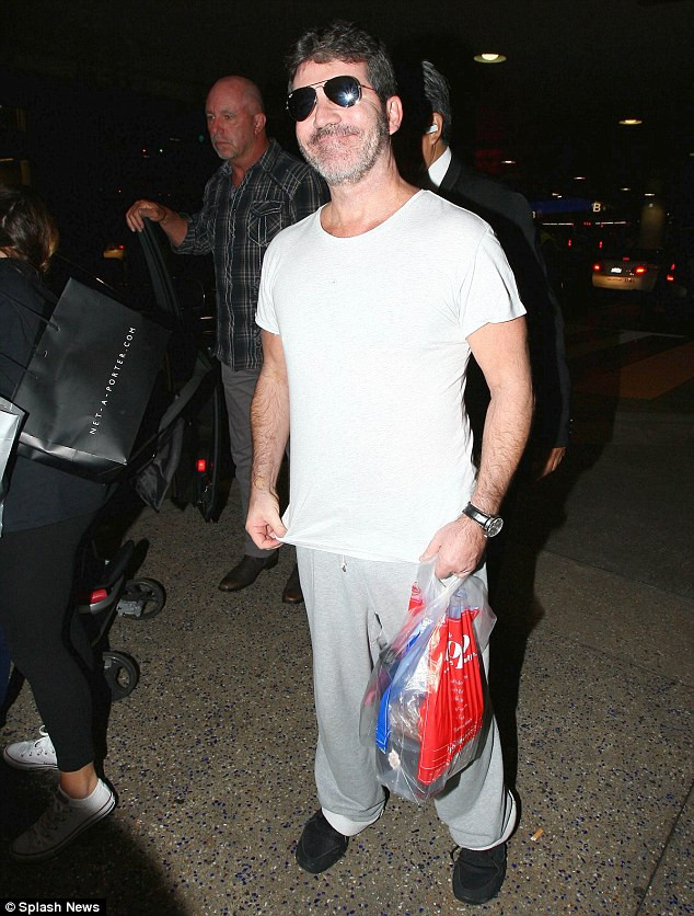 Simon Cowell and Lauren Silverman with their son Eric arriving at LAX