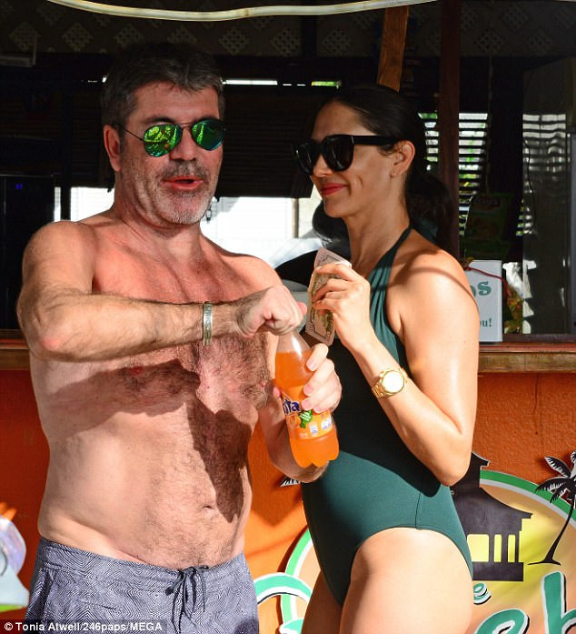 Simon Cowell and Lauren Silverman in Barbados at a bar
