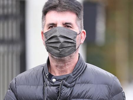 Simon Cowell takes some exercise in rainy London