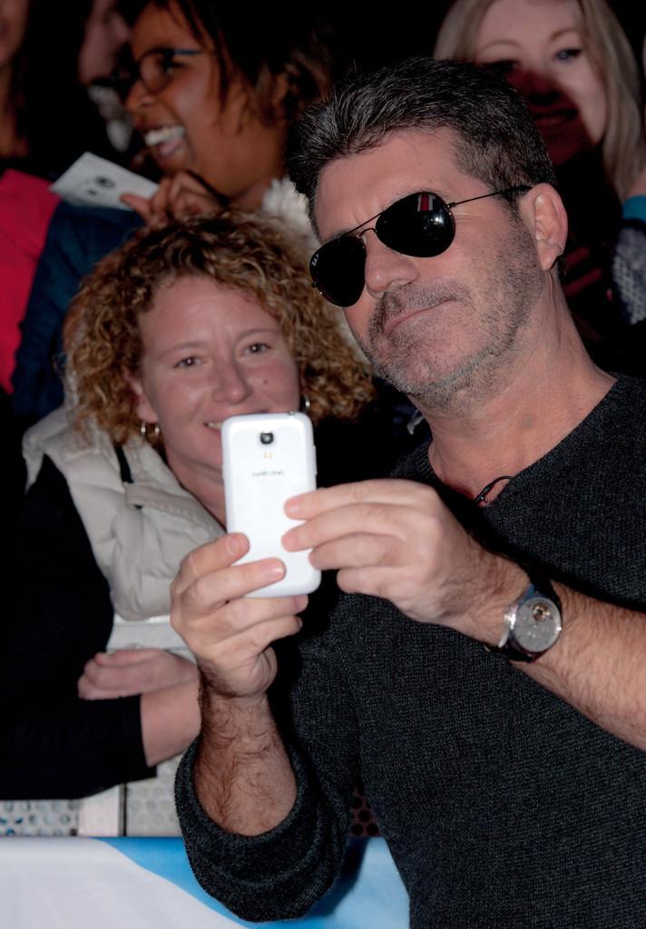 Simon Cowell taking a selfie with a fan