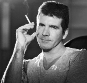 simon cowell poses with a cigarette for a photo shoot