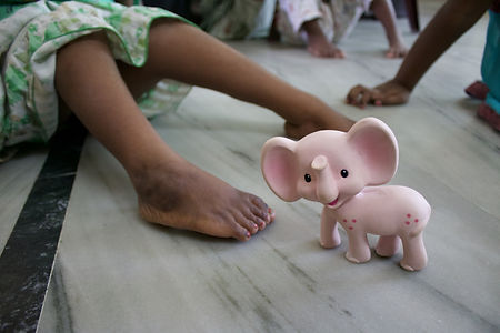 A toy elephant sitting on te floor beside a pair of children's feet