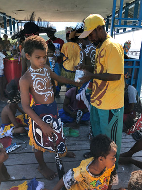 Matan getting painted with traditional Papuan body paint