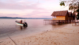 Sunset photo of Yenbuba Homestay's overwater bungalows and Soul Scuba Divers' boat