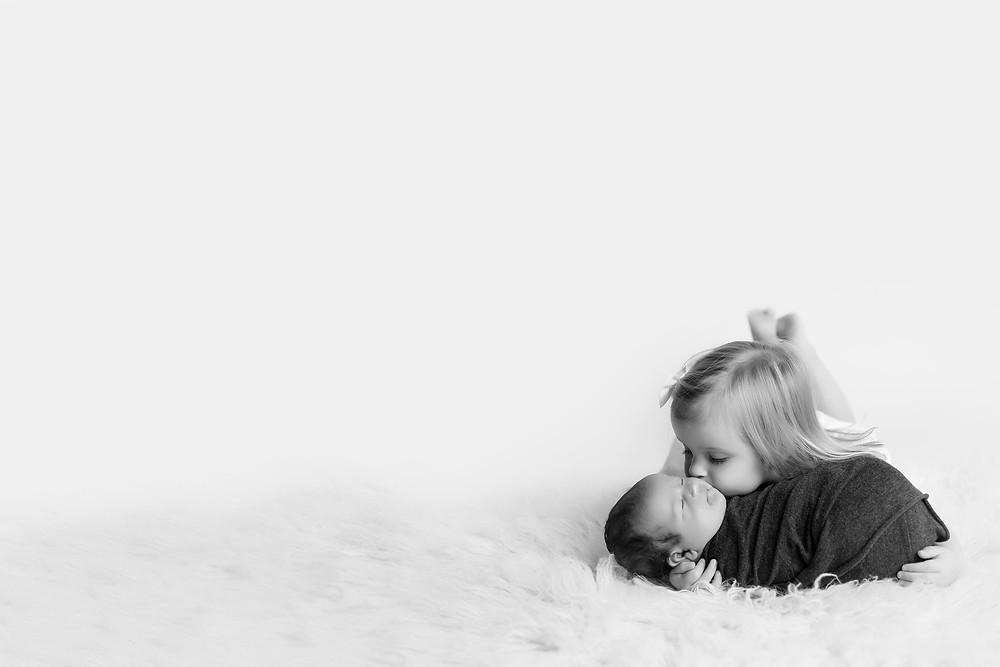 big sister kissing newborn baby brother