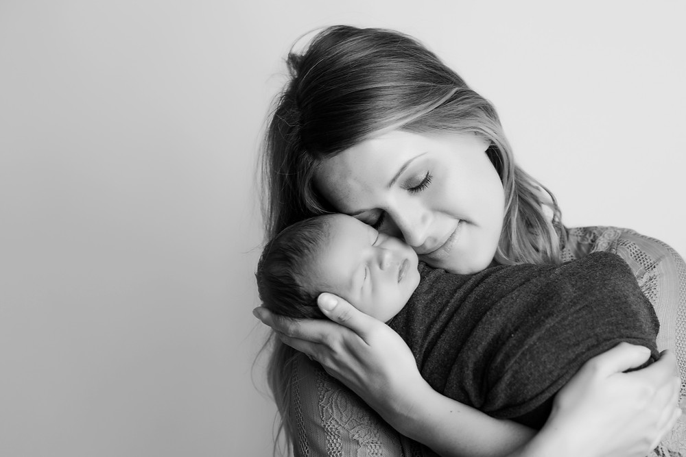 mother snuggling newborn baby boy