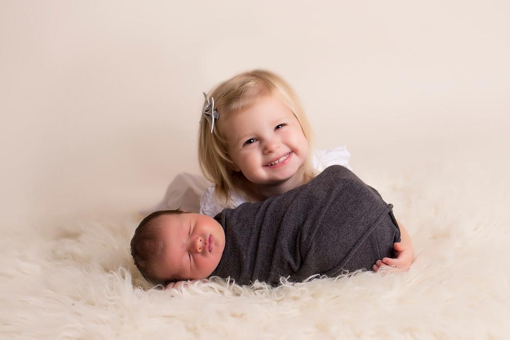 Big sister smiling at newborn baby BennyAni Photography