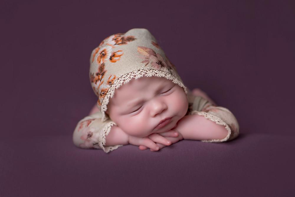 Sleeping Newborn Photograph with Purple Backdrop