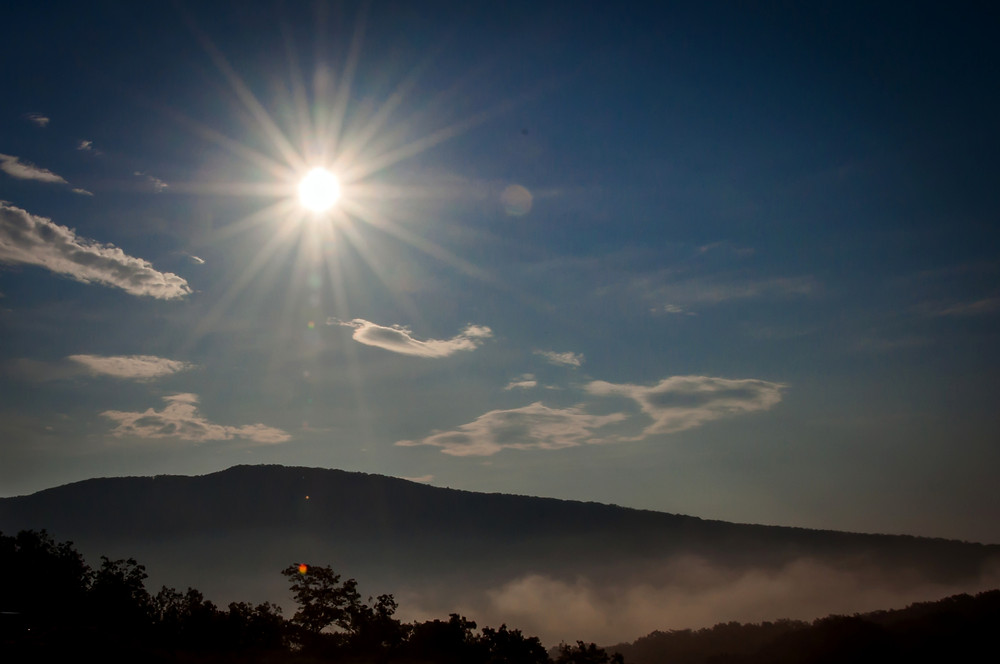 Bright sun with rays over a mountain ridge