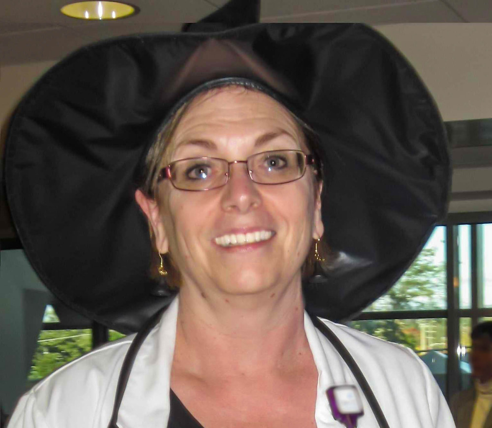 female doctor in black with hat smiling