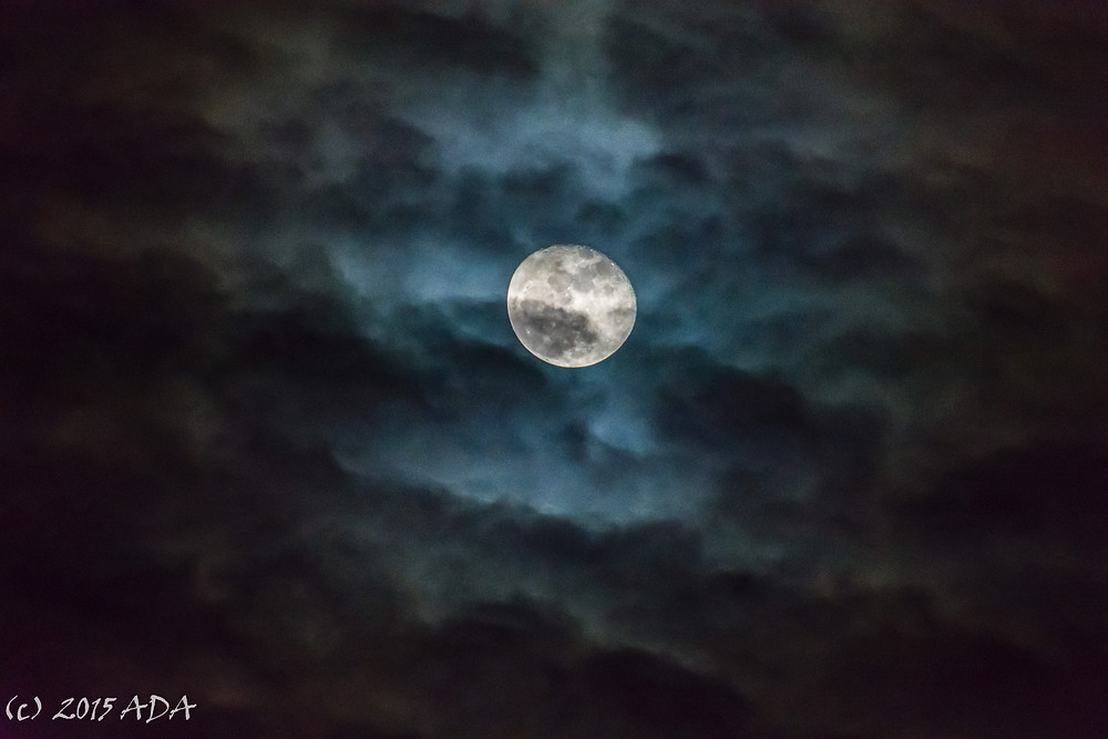 Full moon seen through colorful clouds